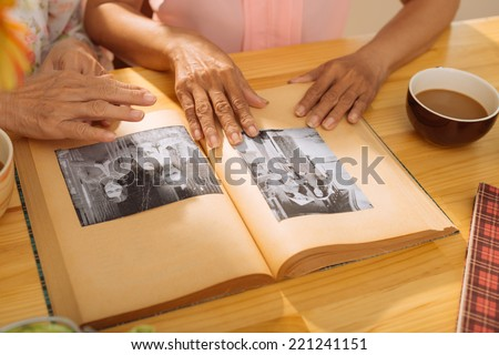 Hands of mature women watching old photos in the - stock photo