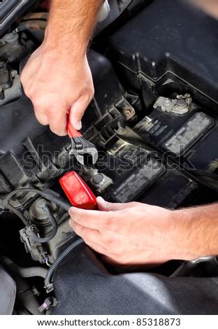 Hands of mechanic working in auto repair shop. - stock photo