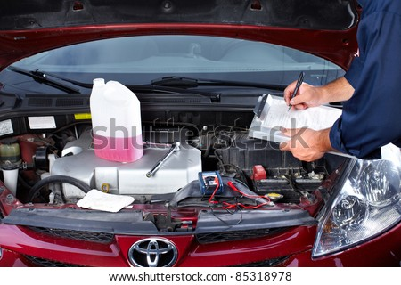 Hands of mechanic working in auto repair shop. - stock photo