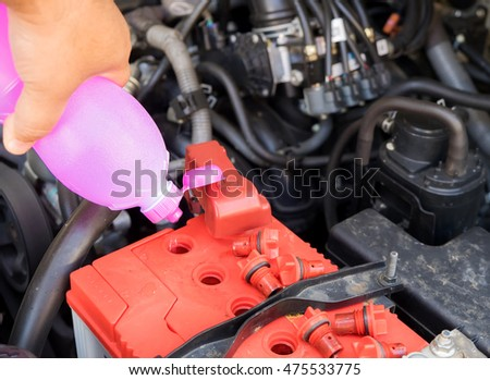 Hands of mechanic working in auto repair shop Add distilled water in battery