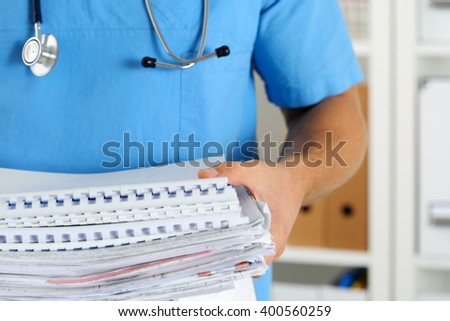 Hands of medicine therapeutist doctor wearing blue uniform holding pile of business papers at work table. Medications consumption account, bureaucracy in hospital work, patient documentation concept - stock photo