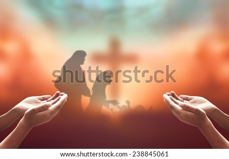 Hands of men praying over blurred The cross and nativity story. - stock photo