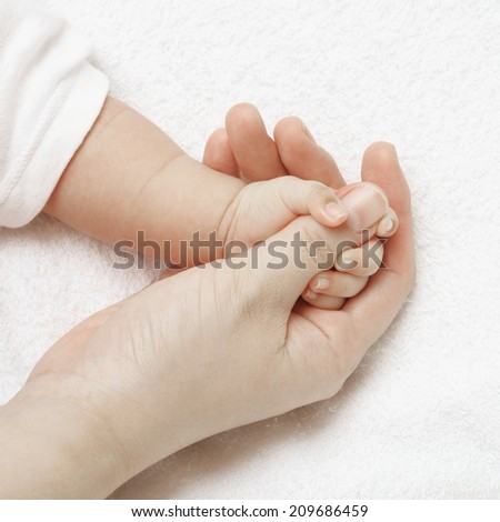 hands of mother and baby - stock photo