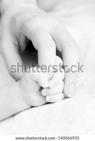 Hands of mother and baby, closeup - stock photo