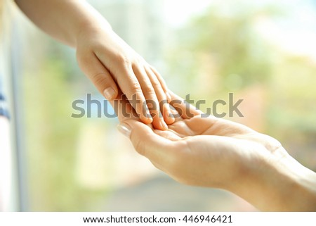 Hands of mother and child on natural background
