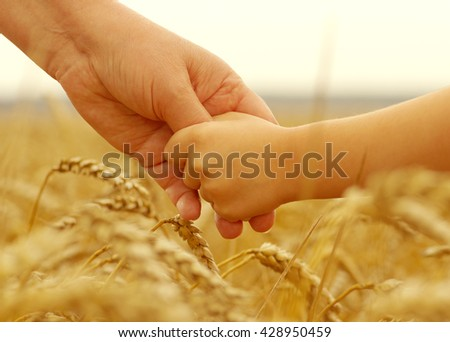Hands of mother and daughter holding each other on wheat field - stock photo