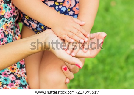Hands of mother and daughter holding each other. Summer park in background - stock photo