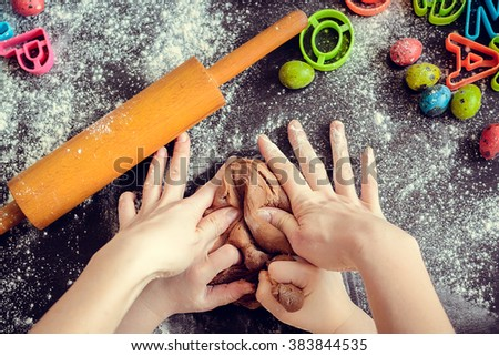 Hands of mother and daughter kneading dough together in the kitchen. Mother teaching daughter how to bake cookies for holidays. Easter baking preparation. Easter food concept. Top view. - stock photo