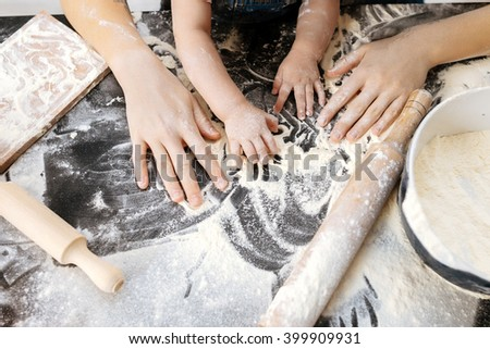 Hands of mother and daughter preparing the dough on the table - stock photo