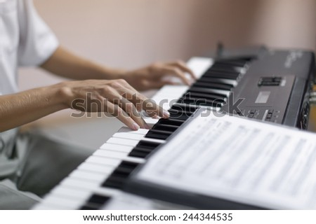 Hands of musician. Pianist playing on a synthesizer indoor. Shoot with shallow depth of field - stock photo