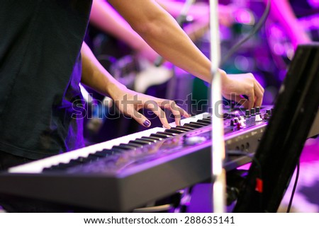 hands of musician playing keyboard in concert with shallow depth of field, focus on left hand - stock photo