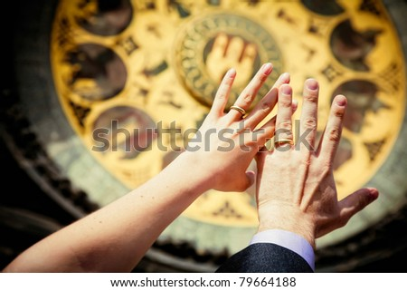 hands of newly married on clock background in Prague - stock photo