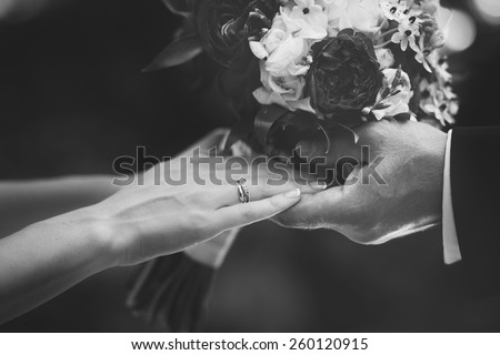 Hands of newlywed couple in love, wedding on summer day.  Picture in black and white.  - stock photo