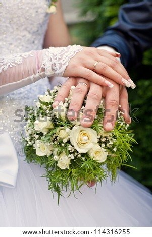 Hands of newlyweds on the wedding bouquet