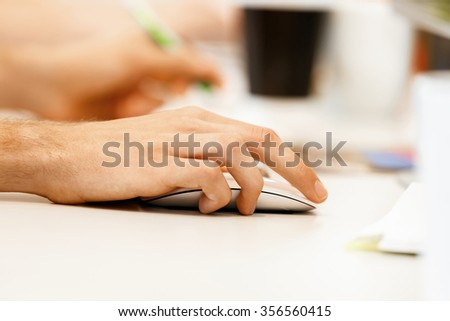 Hands of office worker holding computer mouse - stock photo
