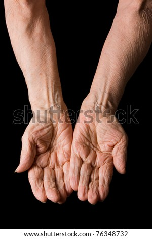 Hands of old elderly woman on black background - stock photo
