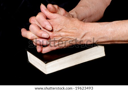Hands of old woman closed in a prayer on bible - stock photo