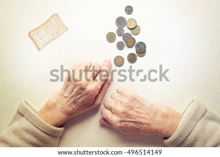 Hands of old woman, counting money (coins of Shekel Israeli ). Small peace of bread lying on the table. Poverty concept.