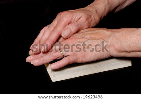 Hands of old woman laying on bible - stock photo