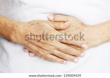 Hands of old woman laying on her