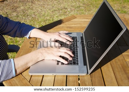 hands of old woman tapping on portable computer - stock photo