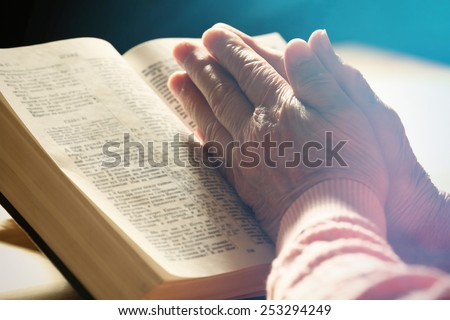 Hands of old woman with Bible on table, close-up - stock photo