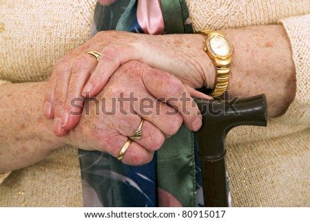 Hands of old woman with walking stick - detail shot.
