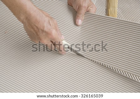 Hands of packer cutting corrugated paperboard paper. Product packaging design