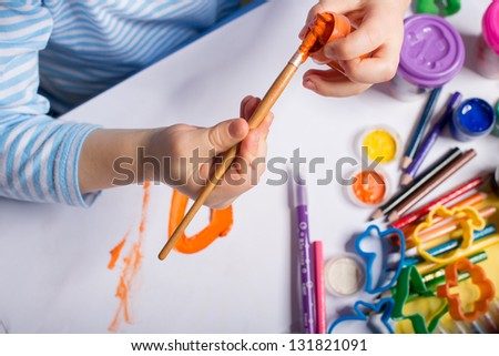Hands of painting little boy and the table for creativity - stock photo