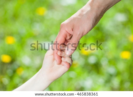 Hands of parent and child holding together on light green background