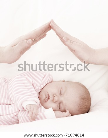 hands of parents combined by a small house over the sleeping baby. The concept of care of children. - stock photo