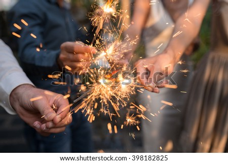 Hands of people holding Bengal light at the party