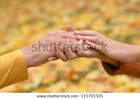 hands of people of different ages in the autumn park - stock photo