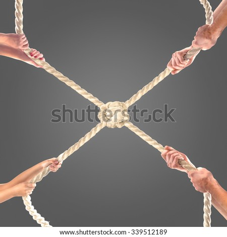Hands of people pulling the rope on black background. Competition concept
