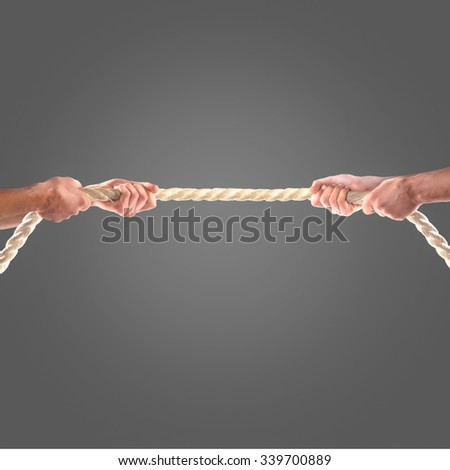 Hands of people pulling the rope on black background.  Competition concept - stock photo