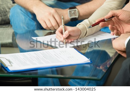 Hands of people signed the document, sitting at the desk - stock photo