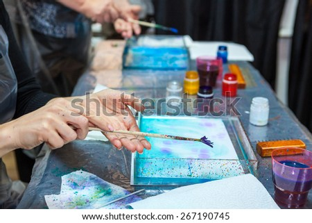 Hands of people which splashing paint over water surface, marbling