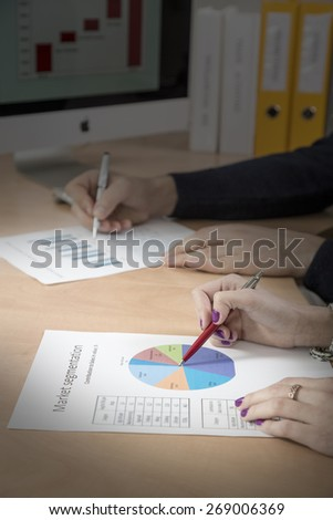 Hands of people working on presentation. Office desk with cropped laptop and large desktop on the foreground, male and female hands keeping pens and pointing on the colored data charts sunbeam - stock photo