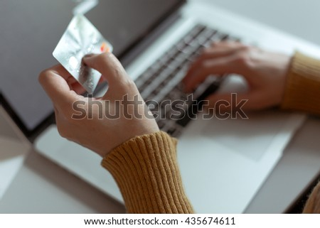 Hands of Person shopping in Internet making instant Payment Transaction at Computer using Credit Card
