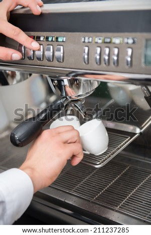 Hands of professional barista holding two white cups on the grating of coffee machine and pushing the button on it - stock photo