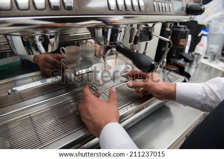 Hands of professional barista standing near the big metal coffee machine and looking how coffee pouring into the white cups - stock photo
