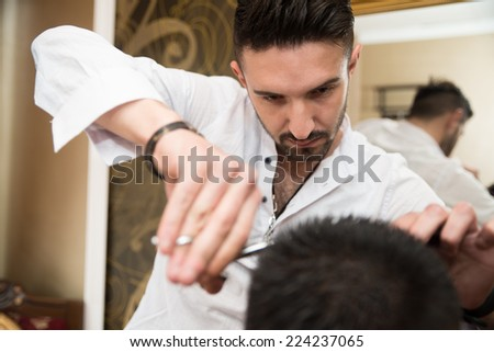 Hands Of Professional Hair Stylist - Handsome Young Hairdresser Giving A New Haircut To Male Customer At Parlor - stock photo