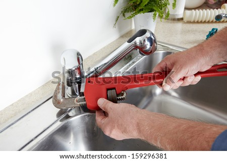 Hands of professional Plumber with a water tap and wrench. - stock photo