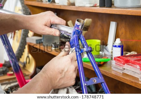 Hands of real bicycle mechanic sanding damaged frame bike in a workshop - stock photo