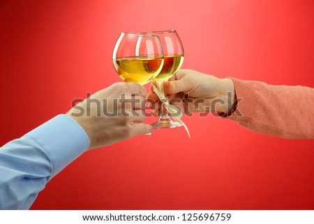 hands of romantic couple toasting their wine glasses, on red background - stock photo