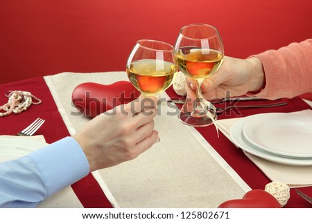 hands of romantic couple toasting their wine glasses over a restaurant table