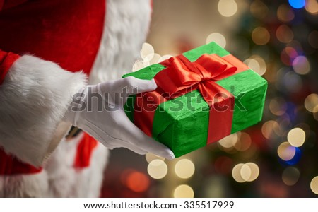 Hands of Santa Claus with Christmas present - stock photo