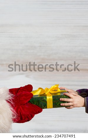 Hands of Santa gives a Christmas gift to hands of child. On wooden background, vertical