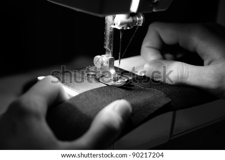 Hands of Seamstress Using Sewing Machine (Monochrome Image) - stock photo