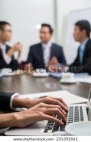 Hands of secretary working on laptop during the business meeting - stock photo